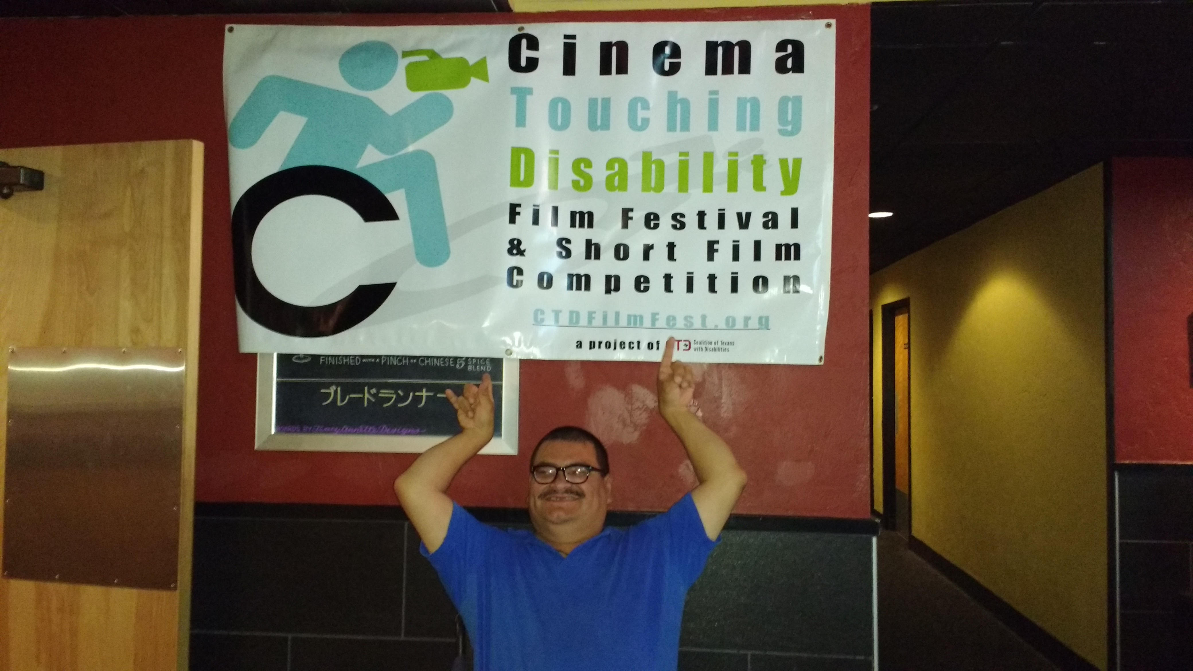 A man in a blue shirt is seated below a Cinema Touching Disability vinyl banner. He smiles broadly and raises both arms overhead to point at the banner.